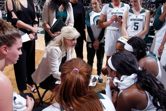 Michigan State coach Suzy Merchant, center, talks to her players during a timeout against Iowa in an NCAA college basketball game, Sunday, Dec. 30, 2018, in East Lansing, Mich. Michigan State won 84-70. (AP Photo/Al Goldis)