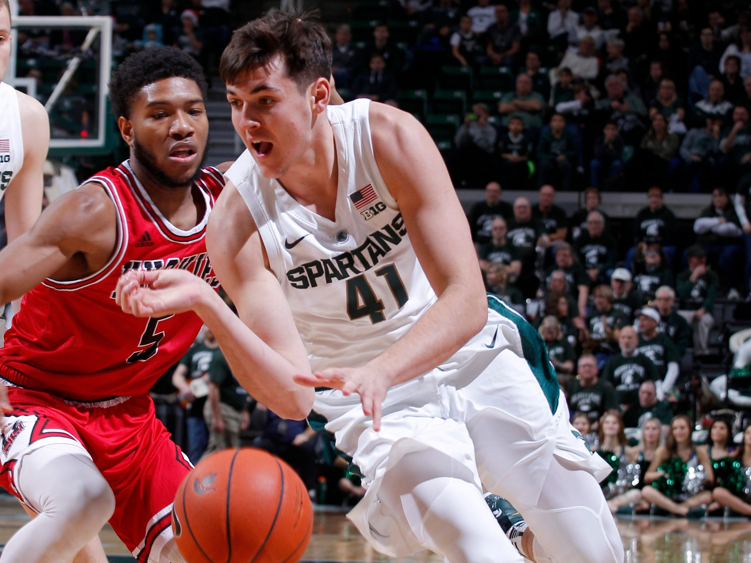 Michigan State's Conner George, right, drives against Northern Illinois' Zaire Mateen, Saturday, Dec. 29, 2018, in East Lansing, Mich.