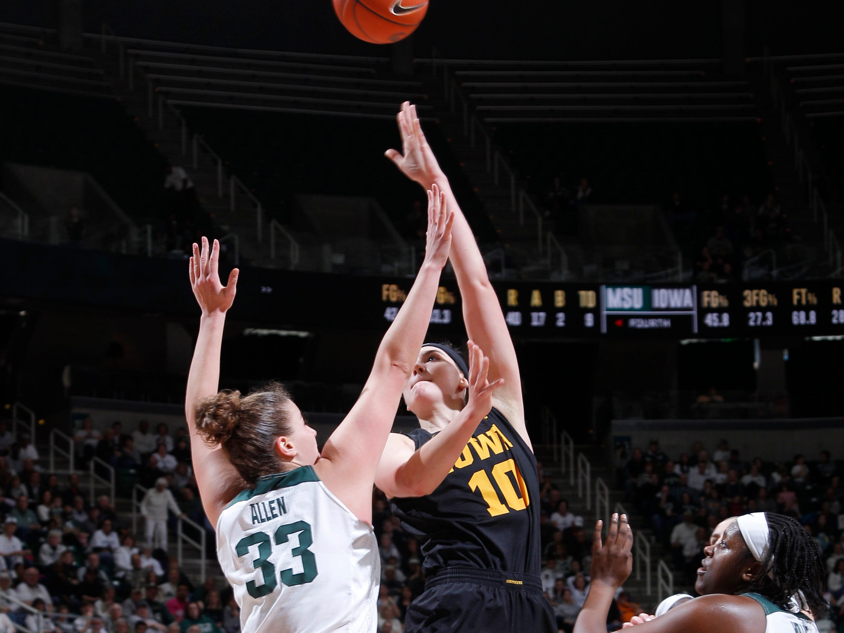 Iowa's Megan Gustafson (10) puts up a shot against Michigan State's Jenna Allen (33) and Nia Hollie (12) during an NCAA college basketball game, Sunday, Dec. 30, 2018, in East Lansing, Mich. Michigan State won 84-70. (AP Photo/Al Goldis)