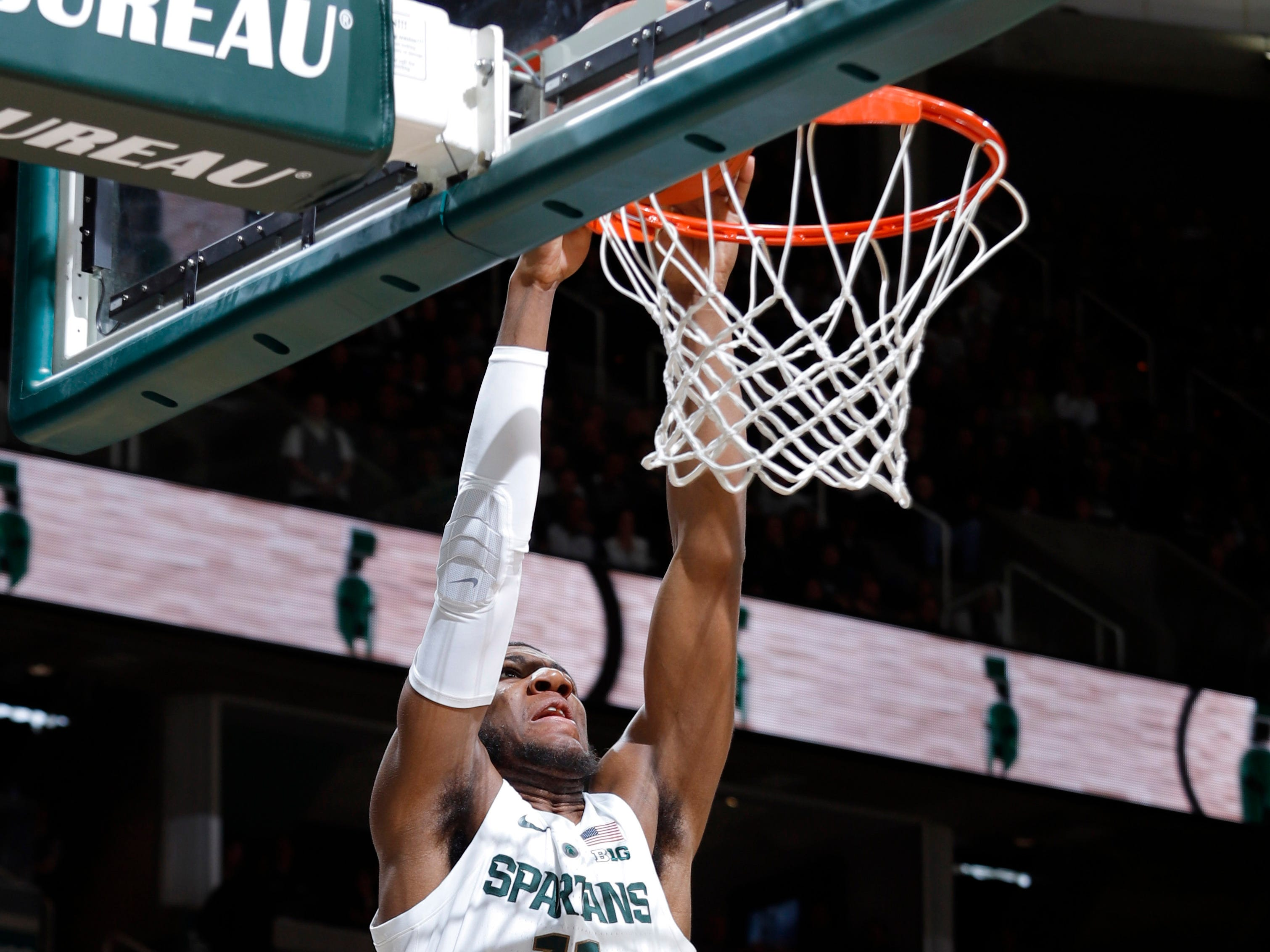 Michigan State's Aaron Henry (11) dunks over Northern Illinois' Gairges Daow (2), Saturday, Dec. 29, 2018, in East Lansing, Mich.