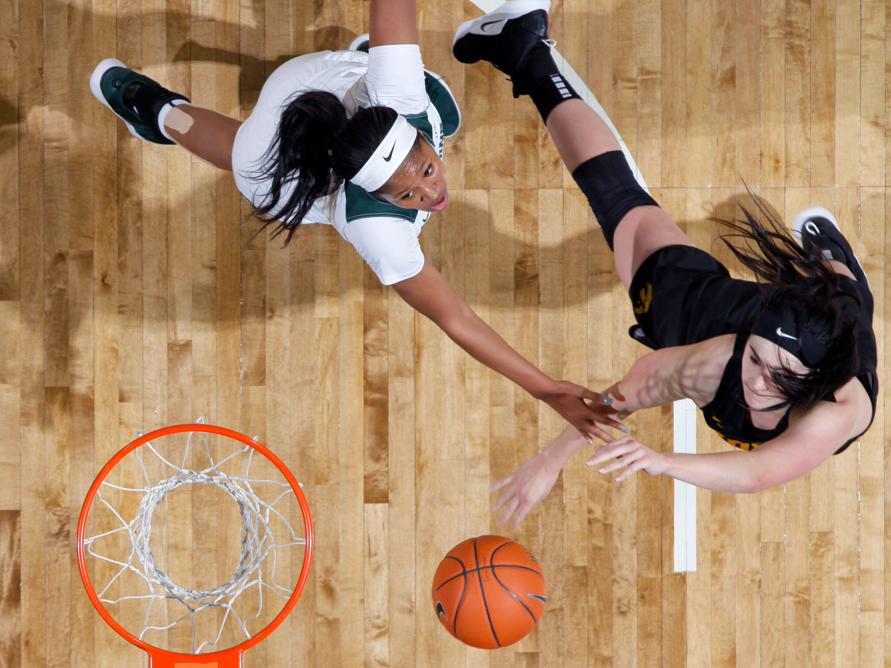 Iowa's Megan Gustafson, right, shoots against Michigan State's Sidney Cooks during an NCAA college basketball game, Sunday, Dec. 30, 2018, in East Lansing, Mich. Michigan State won 84-70. (AP Photo/Al Goldis)