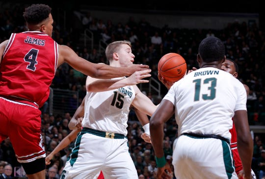 Michigan State's Thomas Kithier (15) and Gabe Brown (13) and Northern Illinois' Lacey James, left, and Austin Richie, right, vie for a rebound, Saturday, Dec. 29, 2018, in East Lansing, Mich.