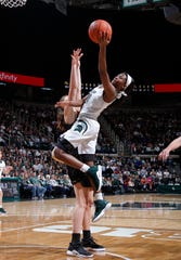 Michigan State's Nia Clouden, right, shoots and draws a foul against Iowa's Amanda Ollinger during an NCAA college basketball game, Sunday, Dec. 30, 2018, in East Lansing, Mich. Michigan State won 84-70. (AP Photo/Al Goldis)