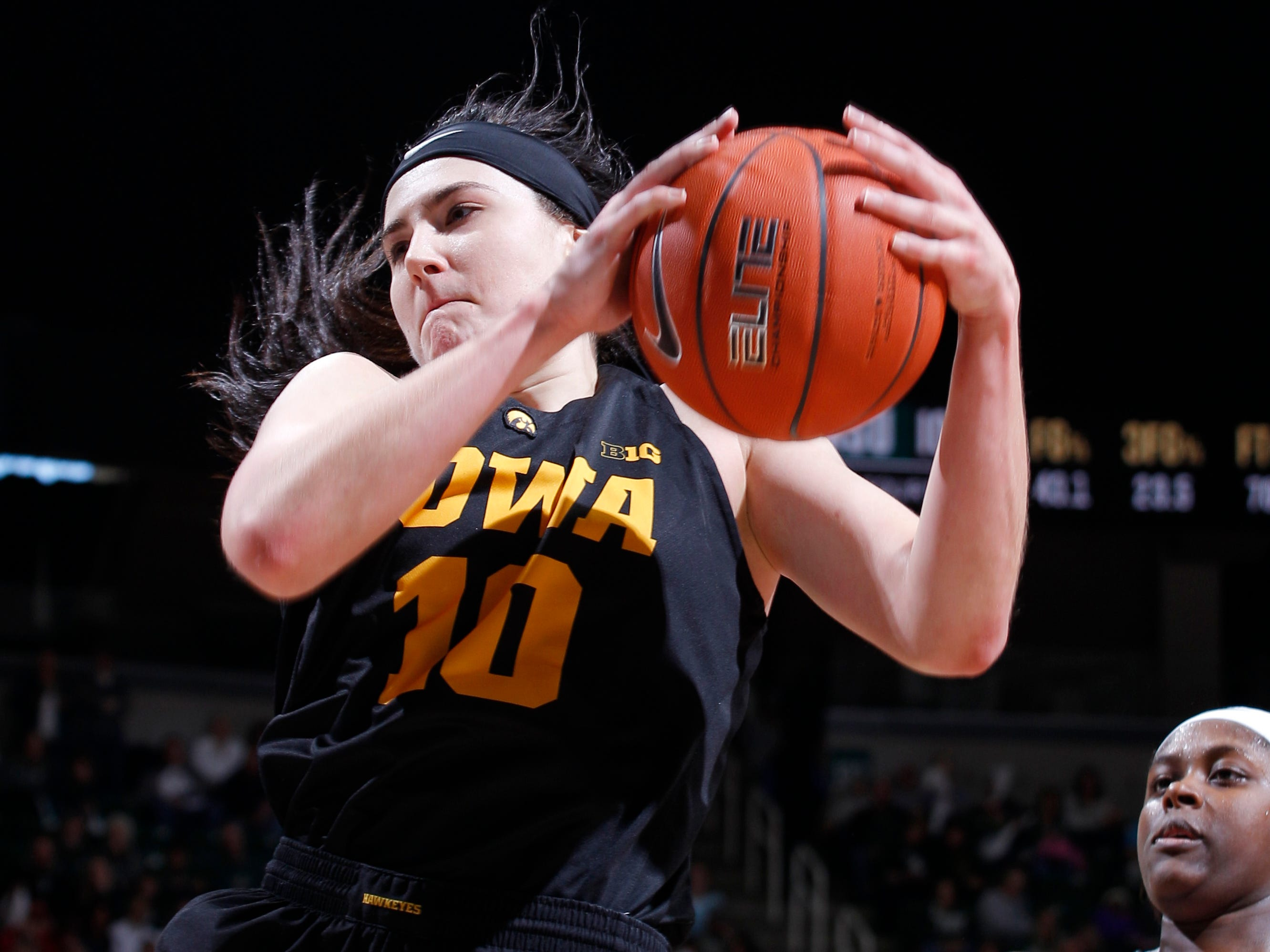 Iowa's Megan Gustafson (10) pulls down a rebound against Michigan State's Nia Hollie during an NCAA college basketball game, Sunday, Dec. 30, 2018, in East Lansing, Mich. Michigan State won 84-70. (AP Photo/Al Goldis)