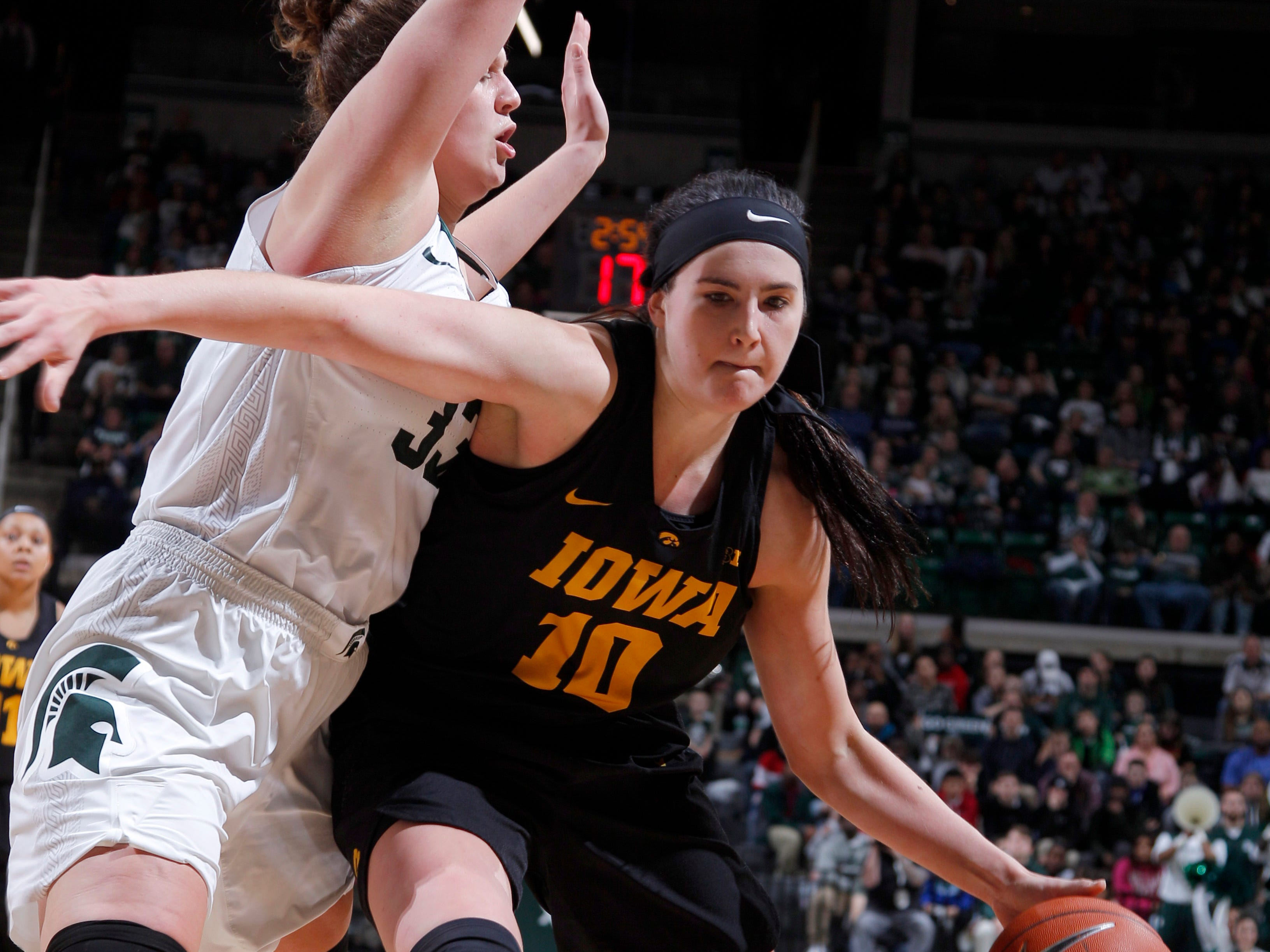 Iowa's Megan Gustafson, right, drives against Michigan State's Jenna Allen during an NCAA college basketball game, Sunday, Dec. 30, 2018, in East Lansing, Mich. Michigan State won 84-70. (AP Photo/Al Goldis)