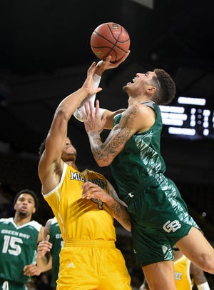 UW-Green Bay guard Sandy Cohen III drives and draws a foul on UW-Milwaukee forward/center Wil Sessoms  in a Horizon League men's basketball game Saturday at the UW-Milwaukee Panther Arena.
