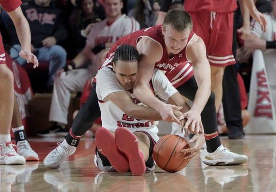 Western Kentucky guard Dalano Banton (20) tries to take control of the ball against Wisconsin guard Brad Davison.