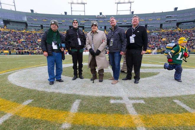 Eugene Nordby (center), who served as a military surgeon during World War II, is honored at midfield before the Green Bay Packers' game against the Detroit Lions at Lambeau Field in Green Bay on Sunday. Nordby is the same age as the Packers - 100 years old.