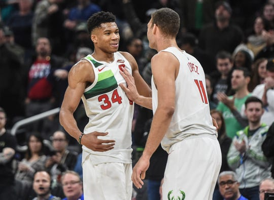 Bucks forward Giannis Antetokounmpo (left) is greeted by center Brook Lopez after Antetokounmpo recorded a triple double.