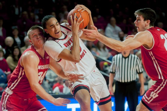 Western Kentucky guard Dalano Banton is double-teamed by Wisconsin guard Brad Davison (left) and forward Ethan Happ during their game Saturday.