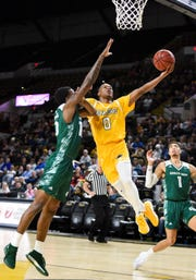 UW-Milwaukee guard Bryce Barnes scores and draws a foul on UW-Green Bay forward Shanquan Hemphill.