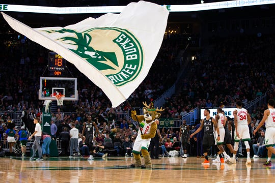 Milwaukee Bucks mascot Bango waves a flag after the Bucks' victory on the mascot's 50th birthday.