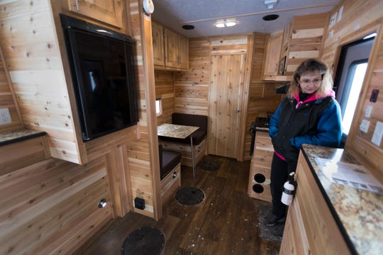 Lori Calaway is shown inside the17-foot Rustic Retreat Edition Ice Castle fish house.