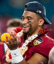 Alabama quarterback Tua Tagovailoa (13) holds an orange after winning the Orange Bowl at Hard Rock Stadium in Miami Gardens, Fla., on Saturday December 29, 2018.