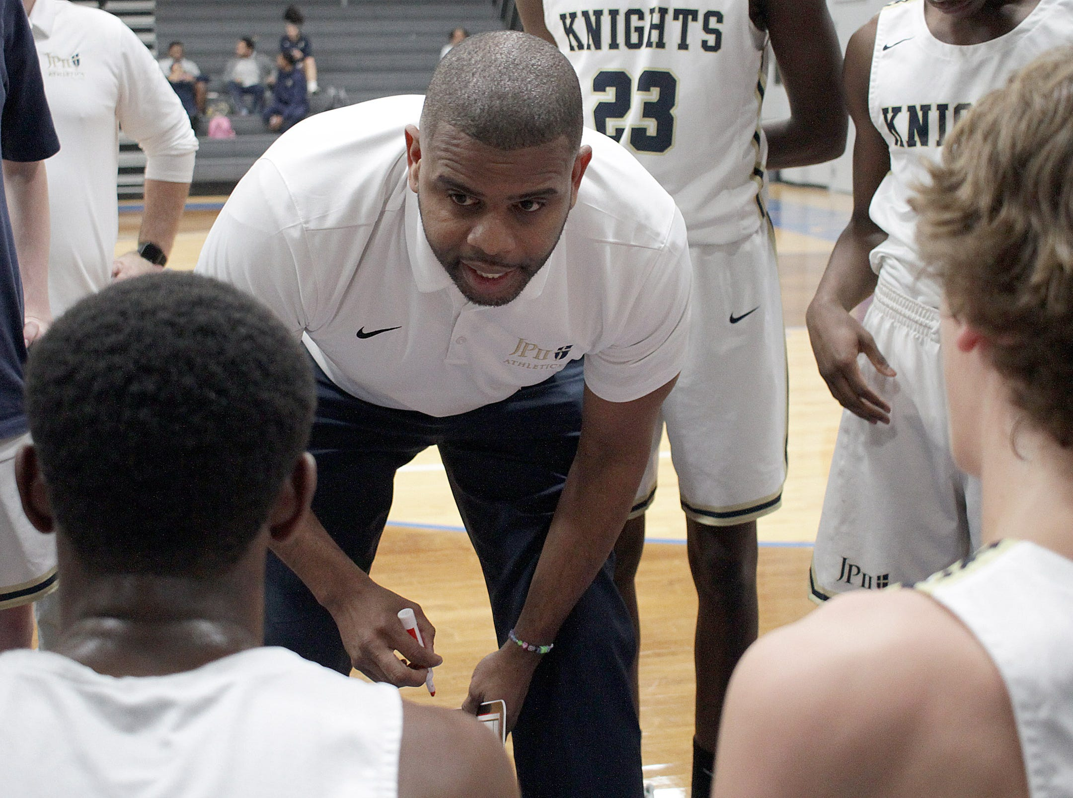 Pope John Paul II coach Charles Wade talks to his team as they play White House on Thursday, December 27, 2018.
