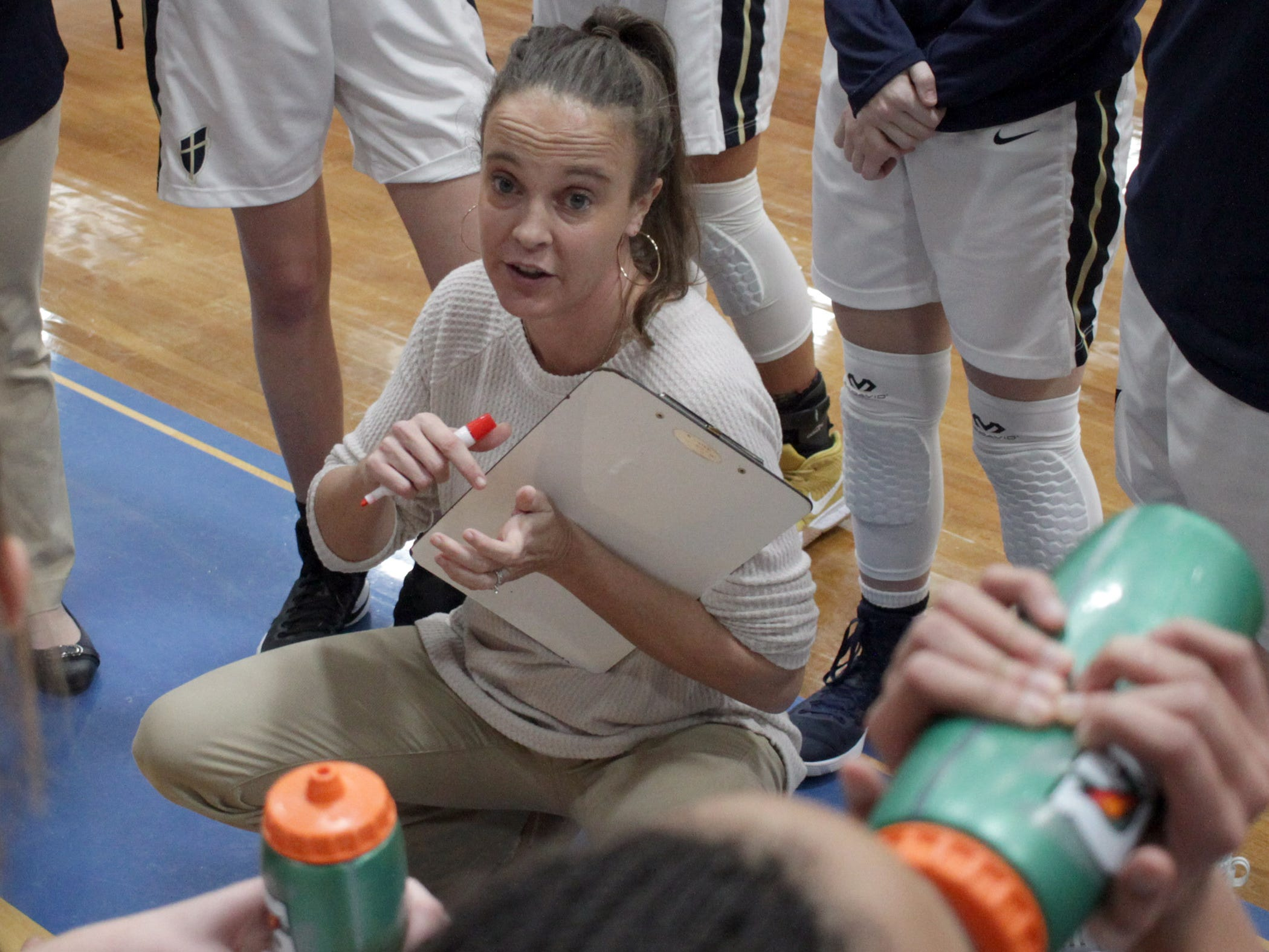 Pope John Paul II coach Angie Puckett speaks to her team as they play White House on Thursday, December 27, 2018.