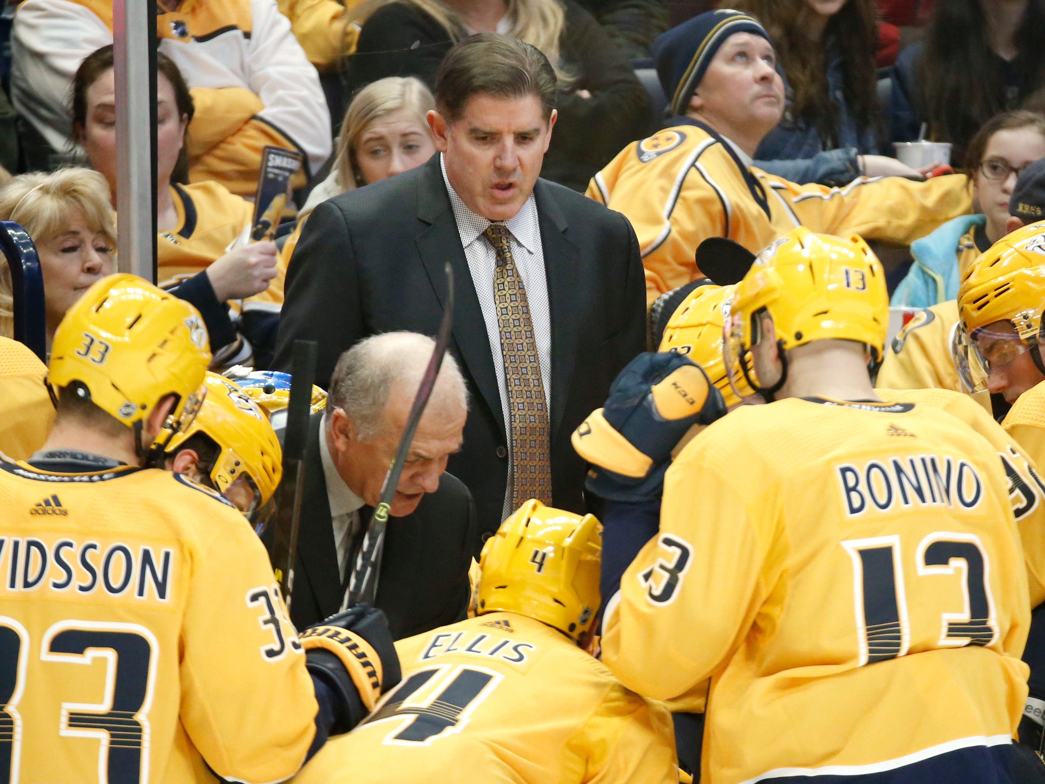 Nashville Predators coach Peter Laviolette, center, talks to players during a timeout in the third period of the team's NHL hockey game against the New York Rangers on Saturday, Dec. 29, 2018, in Nashville, Tenn. The Rangers won 4-3.