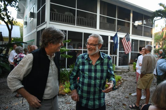 Naples painter Paul Arsenault, left, talks outside his home with fellow painter Richard Segalman. Arsenault and his wife, Eileen, hosted an open house Saturday evening, Dec. 29, 2018, to commemorate the 100th anniversary of their home near the Naples Pier.