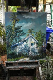 One of many paintings Naples painter Paul Arsenault has painted of his home stands on an easel in the garden. Arsenault and his wife, Eileen, hosted an open house Saturday evening. Dec. 29, 2018, to commemorate the 100th anniversary of their home near the Naples Pier.