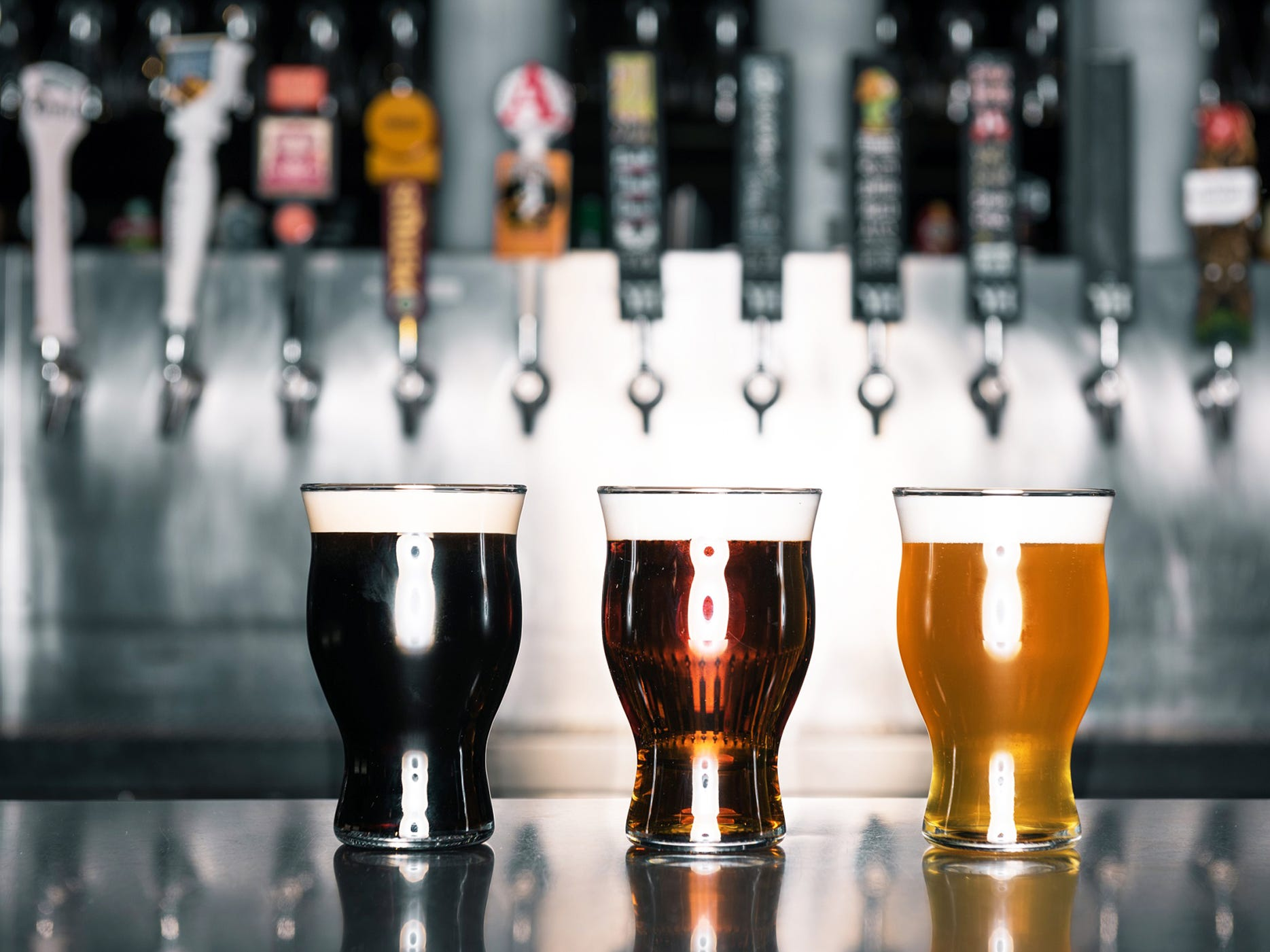 An array of pint glasses, with beer, at a Yard House location.