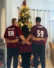 The Allen family shows off their First Baptist Academy football shirts in front of their Christmas tree. From left: Dad Chris Allen, mom Angelica Allen, son Jacob Allen.