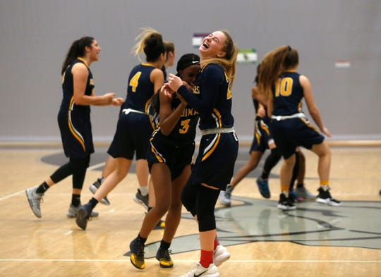 The St. Thomas Aquinas High School girls basketball team celebrates its win against Nease High School during the Naples Holiday Shootout's National Division championship game on Saturday at Gulf Coast High School.