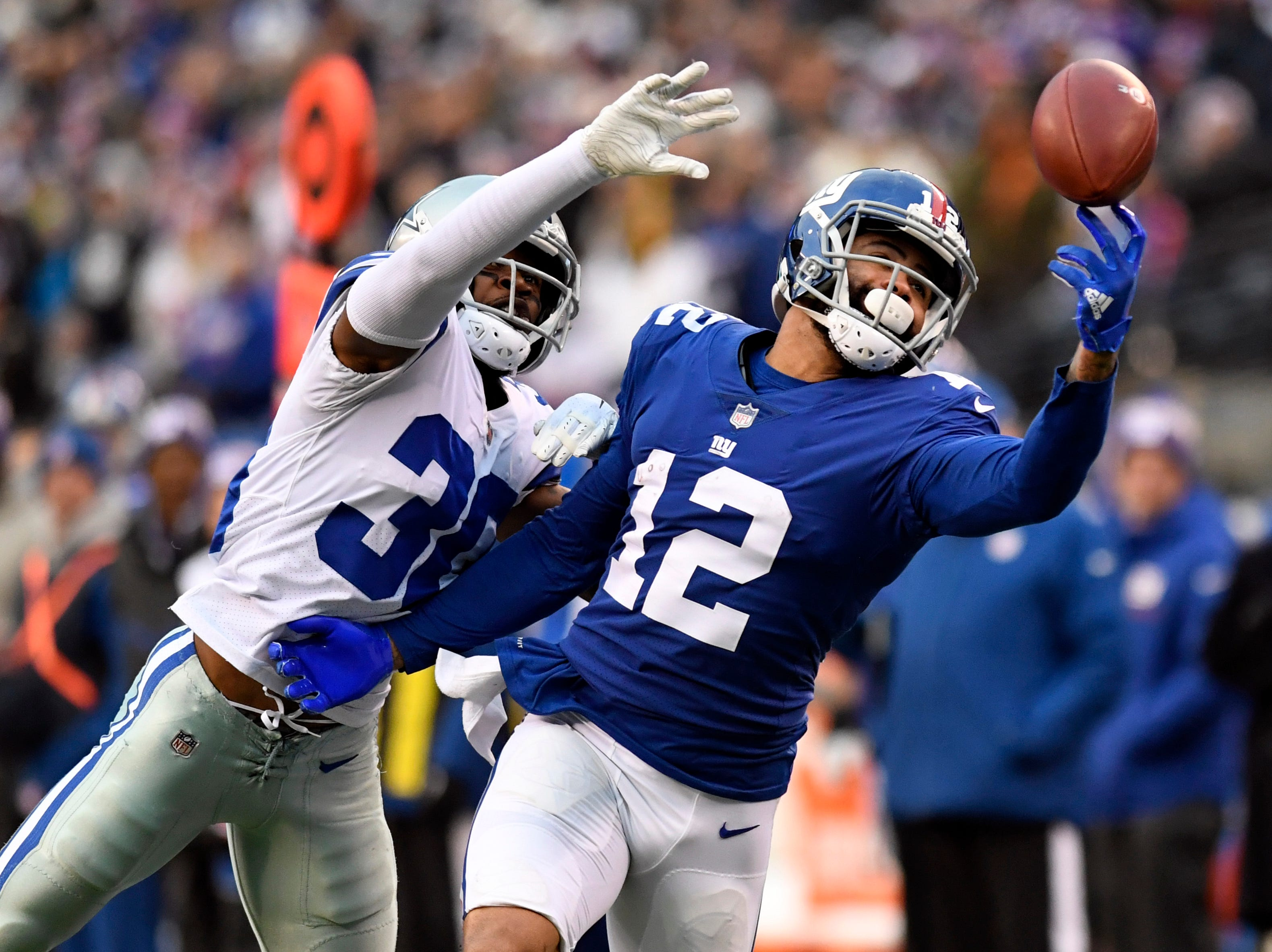 New York Giants wide receiver Cody Latimer (12) juggles the ball before catching it with pressure from Dallas Cowboys cornerback Anthony Brown (30) in the fourth quarter. The New York Giants lose to the Dallas Cowboys 36-35 on Sunday, Dec. 30, 2018, in East Rutherford.