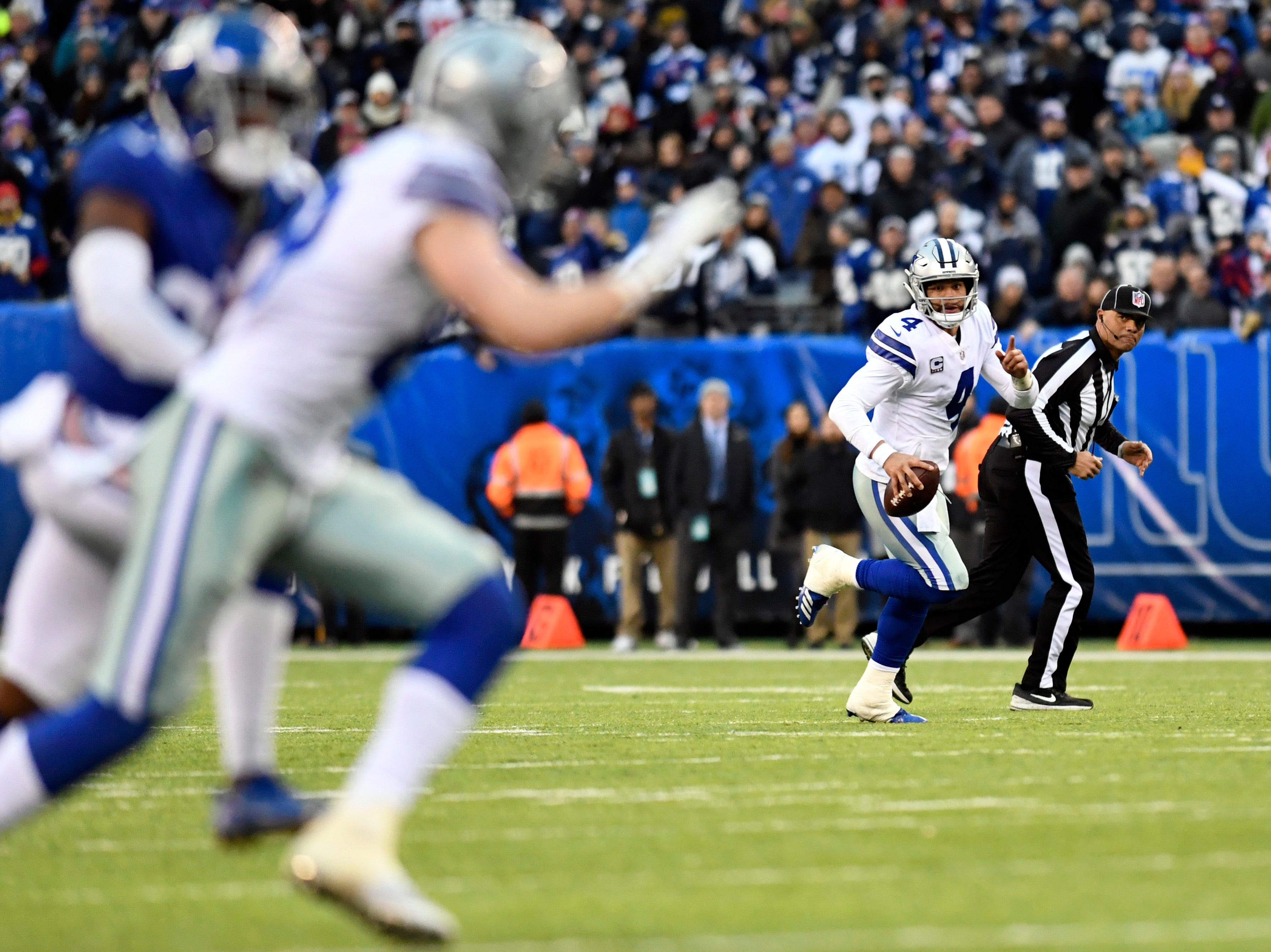 Dallas Cowboys quarterback Dak Prescott (4) gestures to wide receiver Cole Beasley (foreground, left) before throwing a touchdown pass in the fourth quarter. The New York Giants lose to the Dallas Cowboys 36-35 on Sunday, Dec. 30, 2018, in East Rutherford.