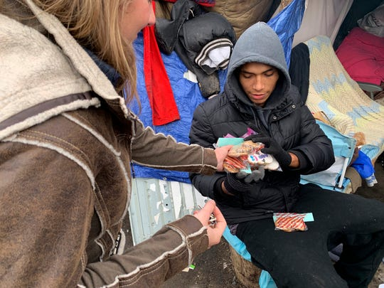 In this Dec. 13, 2018 photo, Kristina Tester, left, hands out cookies made by high school students to residents of a homeless camp made up mainly of Native Americans in south Minneapolis. Tester, who is both a medical student and a law student at the University of Minnesota, grew up near the camp. She began helping at the camp this summer as part of an elective rotation with the Native American Community Clinic in Minneapolis, and continues to volunteer.