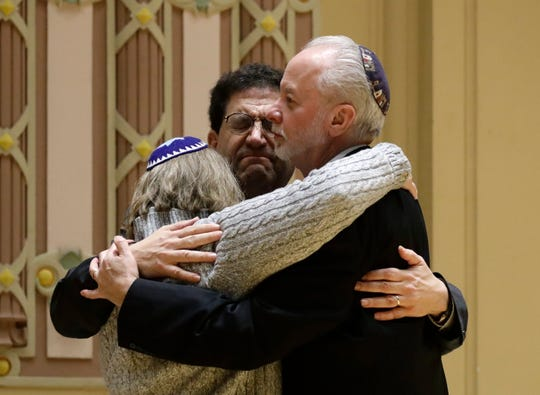 In this Oct. 28, 2018, file photo, Rabbi Jeffrey Myers, right, of Tree of Life/Or L'Simcha Congregation hugs Rabbi Cheryl Klein, left, of Dor Hadash Congregation and Rabbi Jonathan Perlman during a community gathering held in the aftermath of a deadly shooting at the Tree of Life Synagogue in Pittsburgh. As the Jewish community grieved, Myers took a leading role during public memorials and presided over seven funerals in the space of less than a week.