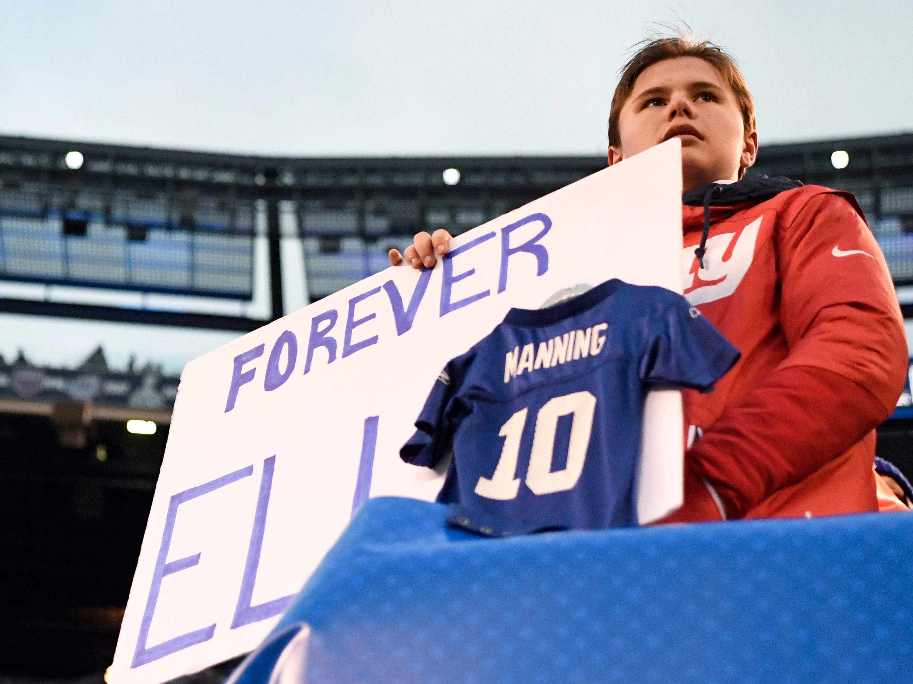 """A young Giants fan holds a sign reading """"Forever Eli"""" as the Giants lose to the Dallas Cowboys 36-35 on Sunday, Dec. 30, 2018, in East Rutherford."""
