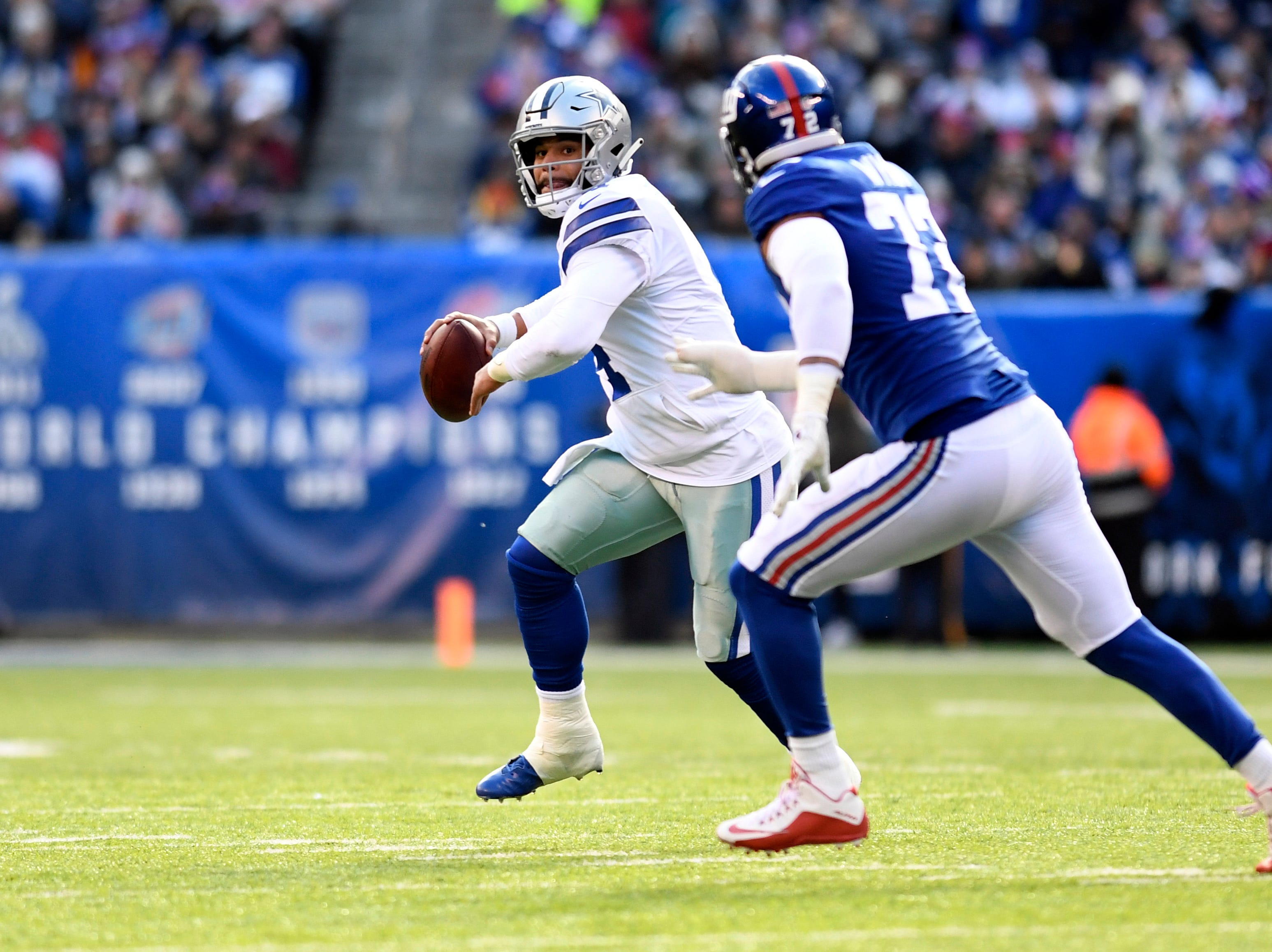 Dallas Cowboys quarterback Dak Prescott (4) looks for an open receiver with pressure from New York Giants defensive end Kerry Wynn (72) in the first half. The New York Giants face the Dallas Cowboys in the last regular season game on Sunday, Dec. 30, 2018, in East Rutherford.