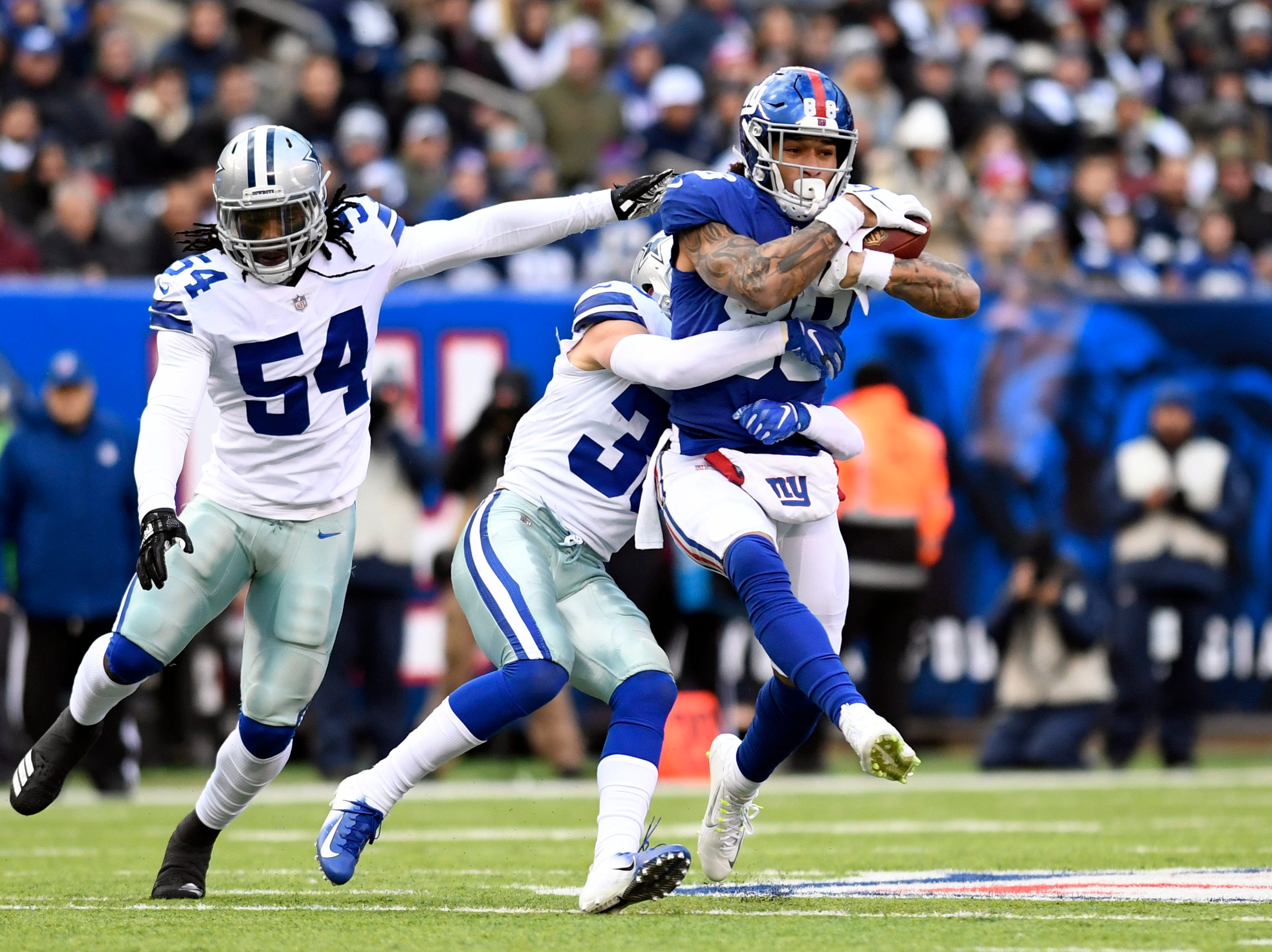 New York Giants tight end Evan Engram (88) completes a pass with pressure from the Cowboys defense. The New York Giants face the Dallas Cowboys in the last regular season game on Sunday, Dec. 30, 2018, in East Rutherford.