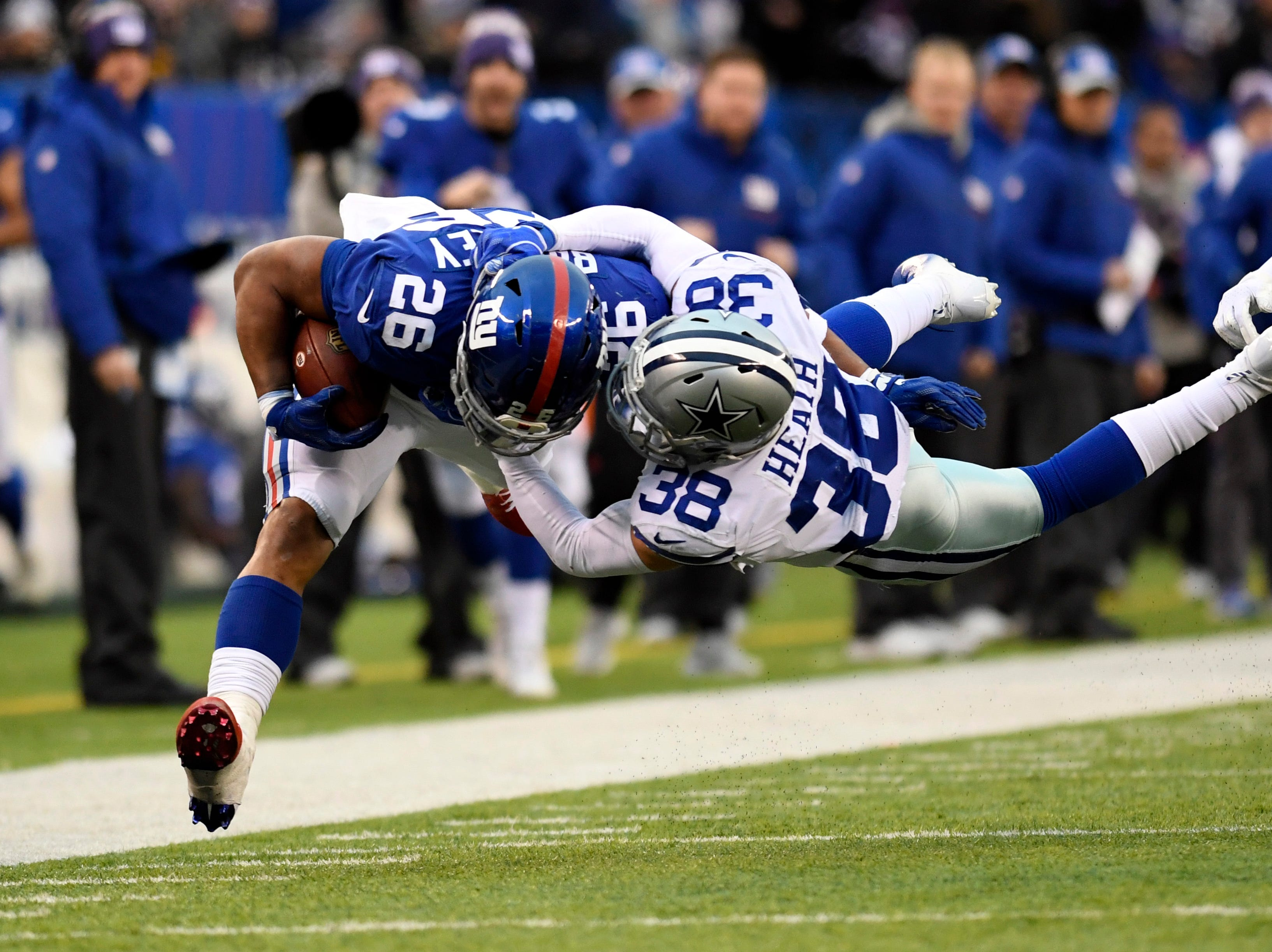 New York Giants running back Saquon Barkley (26) is tackled by Dallas Cowboys strong safety Jeff Heath (38) in the second half. The New York Giants lose to the Dallas Cowboys 36-35 on Sunday, Dec. 30, 2018, in East Rutherford.