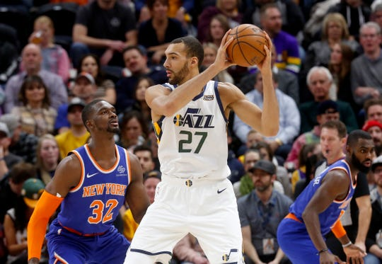 Utah Jazz's Rudy Gobert (27) looks to pass the ball as New York Knicks' Noah Vonleh (32) defends in the first half of an NBA basketball game on Saturday, Dec. 29, 2018, in Salt Lake City.