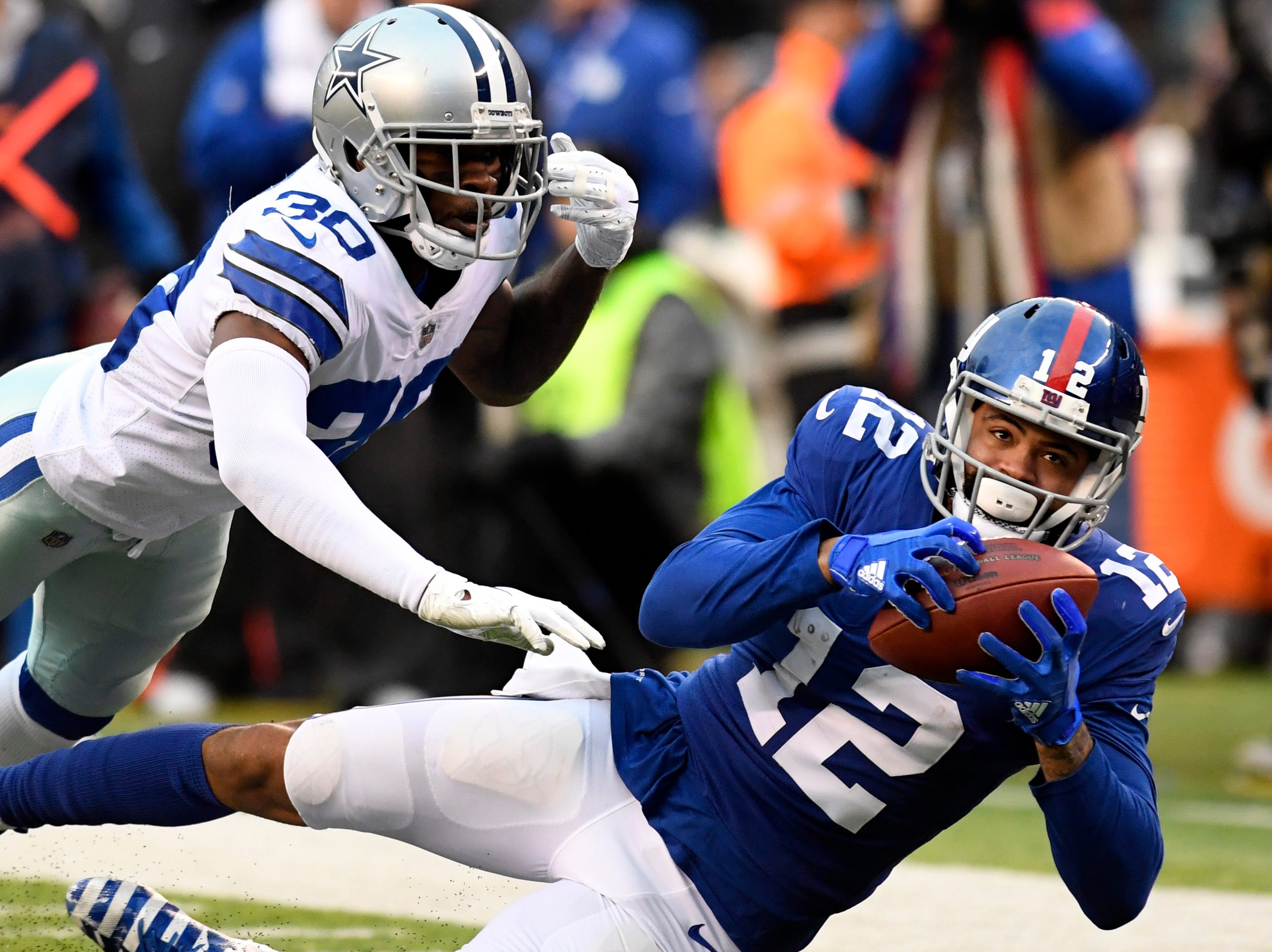 New York Giants wide receiver Cody Latimer (12) comes down with the ball with pressure from Dallas Cowboys cornerback Anthony Brown (30) in the fourth quarter. The New York Giants lose to the Dallas Cowboys 36-35 on Sunday, Dec. 30, 2018, in East Rutherford.