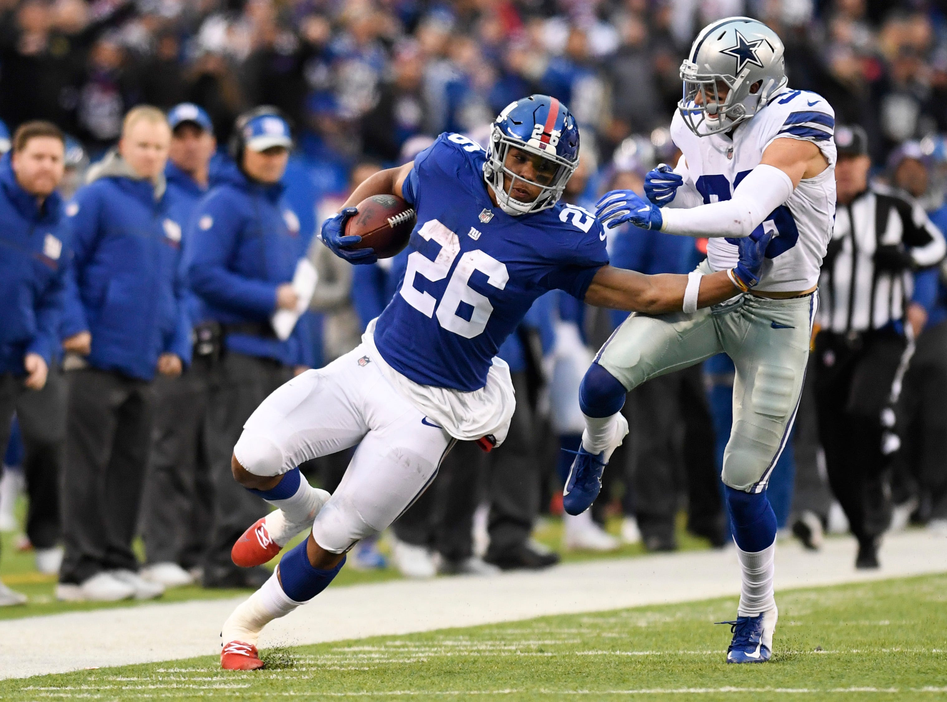New York Giants running back Saquon Barkley (26) stiff-arms Dallas Cowboys strong safety Jeff Heath (38) in the second half. The New York Giants lose to the Dallas Cowboys 36-35 on Sunday, Dec. 30, 2018, in East Rutherford.
