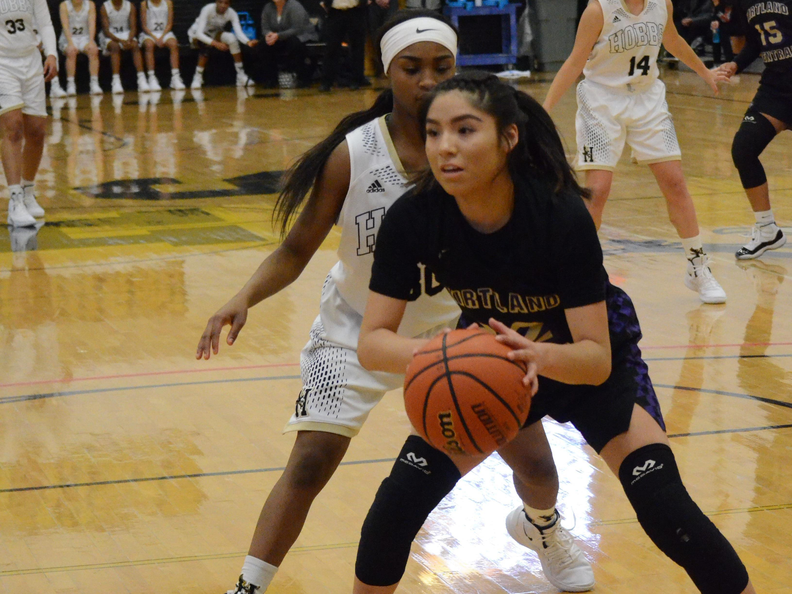Kirtland Central's Tatelyn Manheimer looks to pass the ball down the left side against A'Niya Heckard (30) of Hobbs during Saturday's Hobbs Holiday Tournament championship game at Tasker Arena.