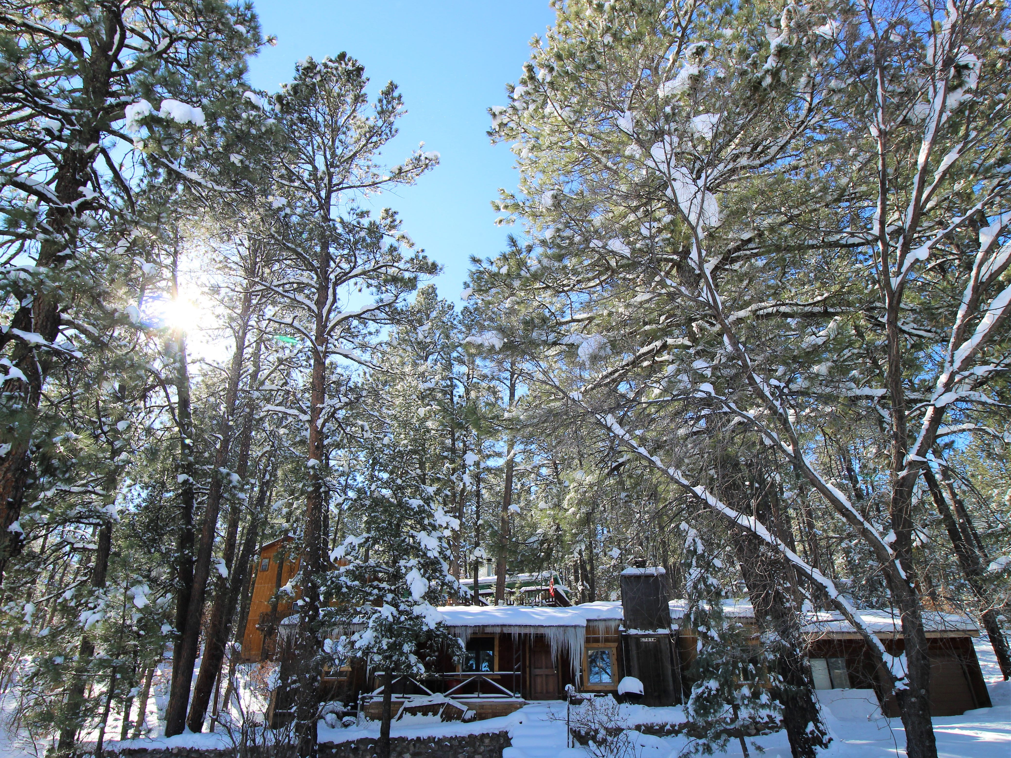 A home is covered with snow and ice after a major storm hit Ruidoso.