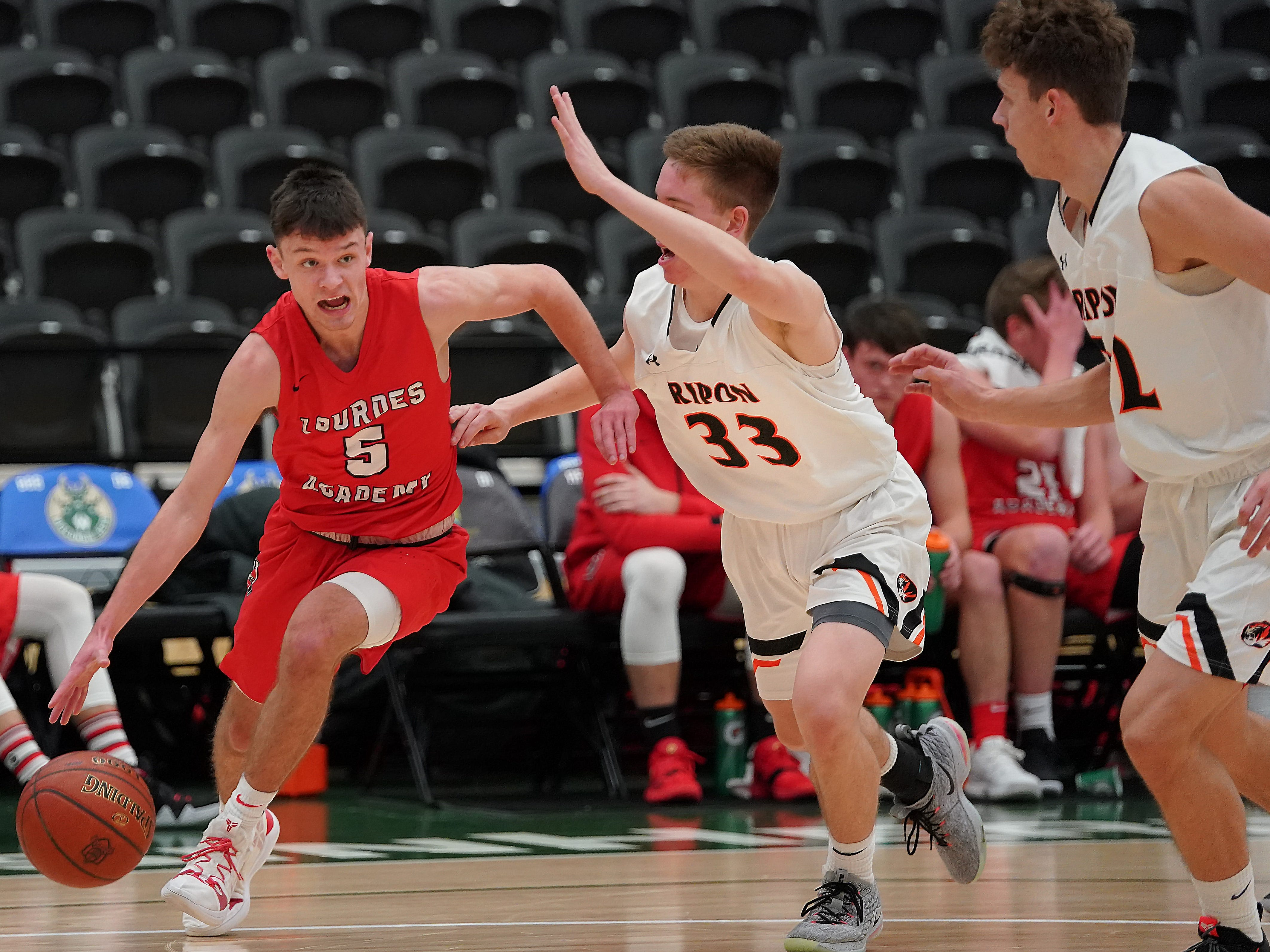 Jack McKellips (5) of Lourdes drives past Garrett Jennings (33) of Ripon. The Lourdes Knights and Ripon Tigers met in a nonconference basketball game Saturday afternoon, December 29, 2018 at the Menomonie Nation Arena in Oshkosh.