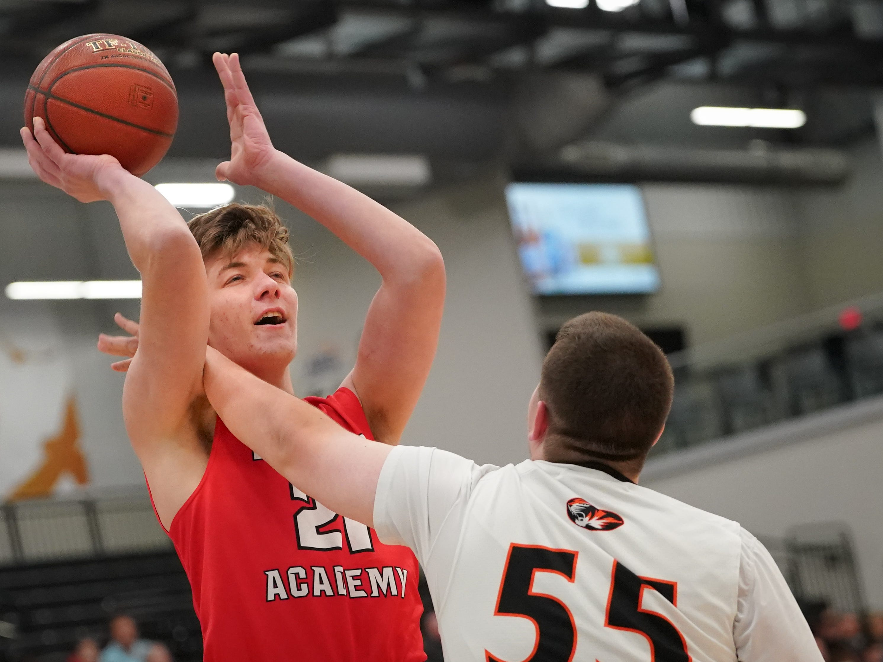 George Muench (21) of Lourdes tries to get a shot while blocked by Jackson Morrin (55) of Ripon. The Lourdes Knights and Ripon Tigers met in a nonconference basketball game Saturday afternoon, December 29, 2018 at the Menomonie Nation Arena in Oshkosh.