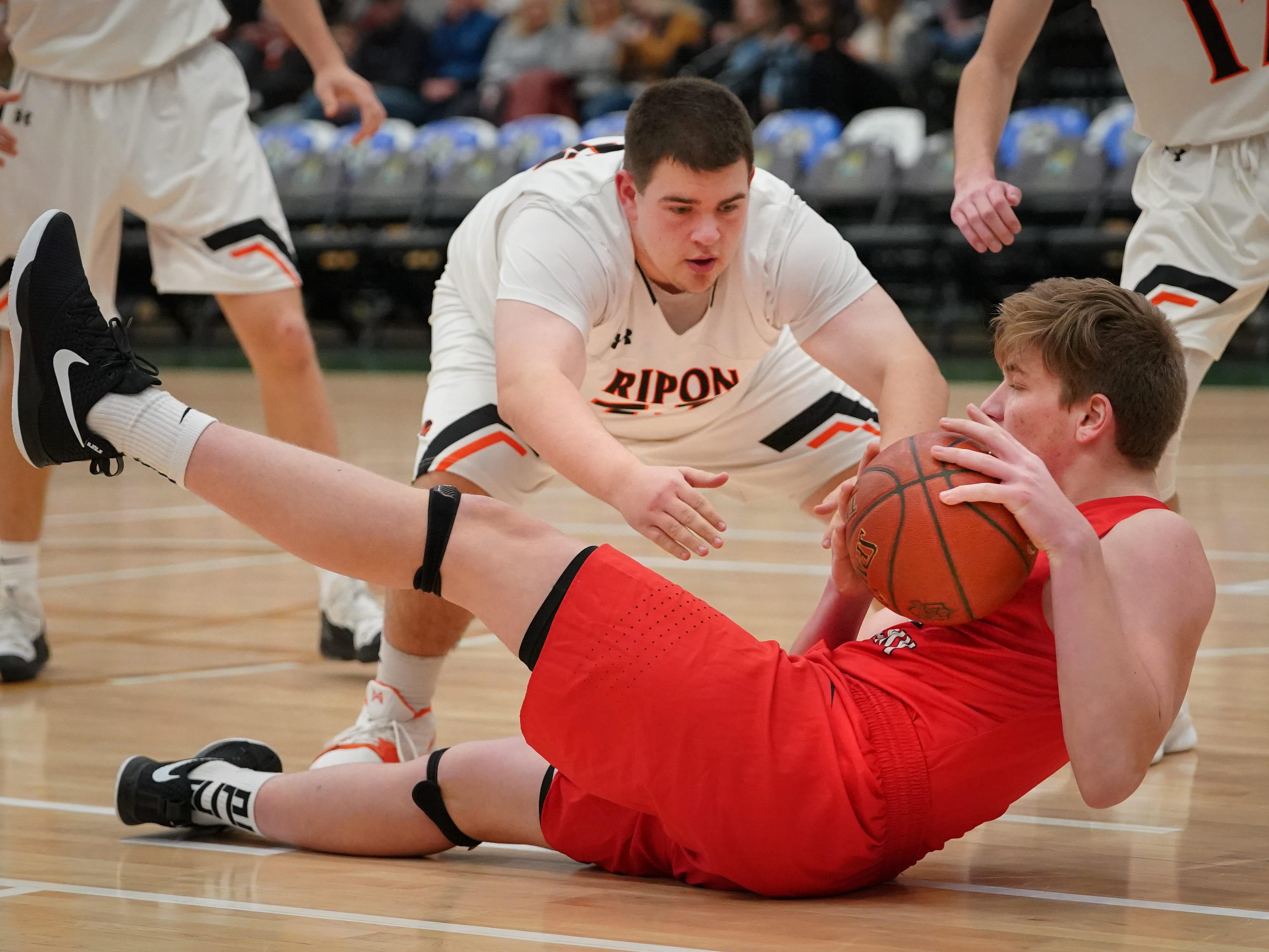 George Muench (21) of Lourdes tries to keep the ball away from Jackson Morrin (55) of Ripon. The Lourdes Knights and Ripon Tigers met in a nonconference basketball game Saturday afternoon, December 29, 2018 at the Menomonie Nation Arena in Oshkosh.