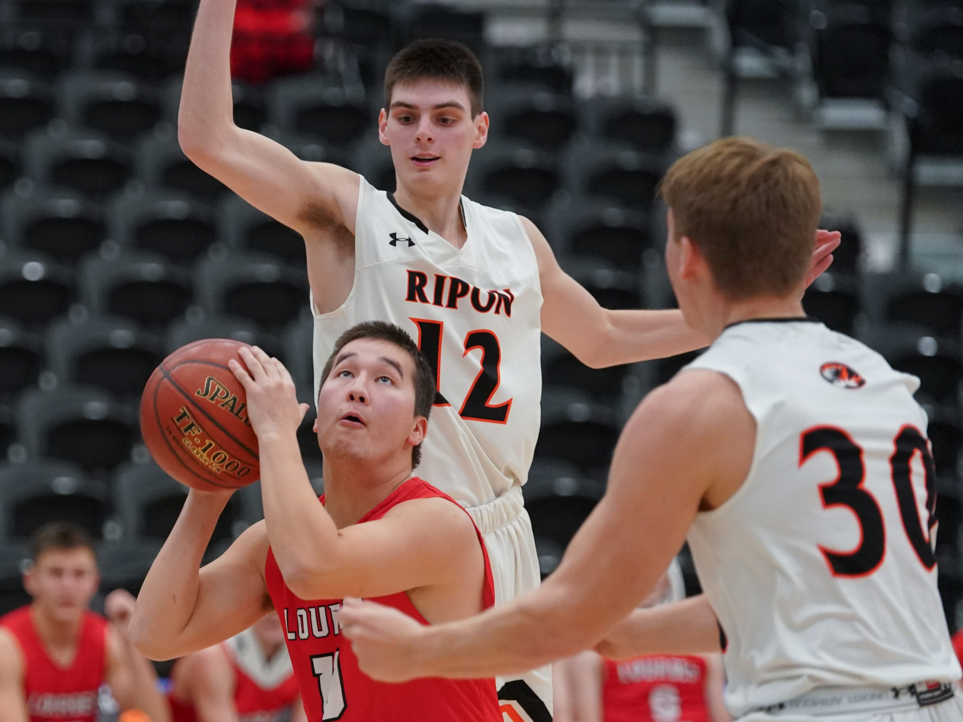Ben Sydlik (10) of Lourdes tries to get a shot off in front of Luke Rogers (12) of Ripon. The Lourdes Knights and Ripon Tigers met in a nonconference basketball game Saturday afternoon, December 29, 2018 at the Menomonie Nation Arena in Oshkosh.
