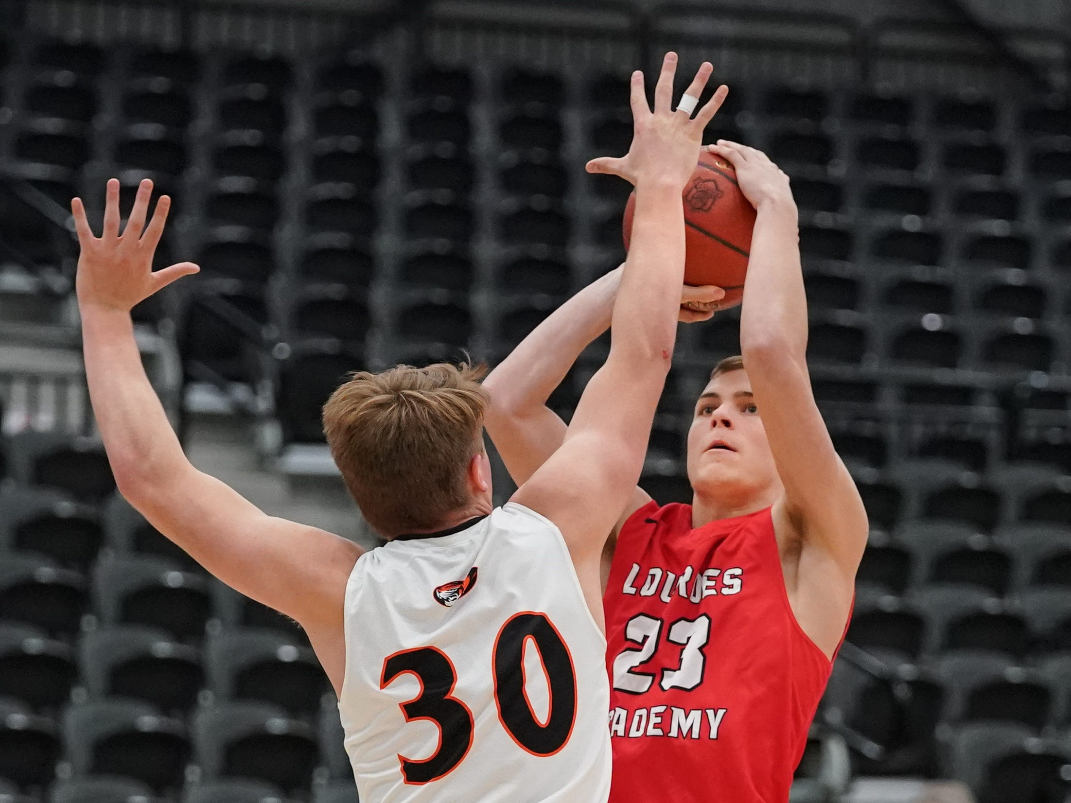 Max Husboe (30) of Ripon tries to block a shot by Nathan Kaull (23) of Lourdes. The Lourdes Knights and Ripon Tigers met in a nonconference basketball game Saturday afternoon, December 29, 2018 at the Menomonie Nation Arena in Oshkosh.