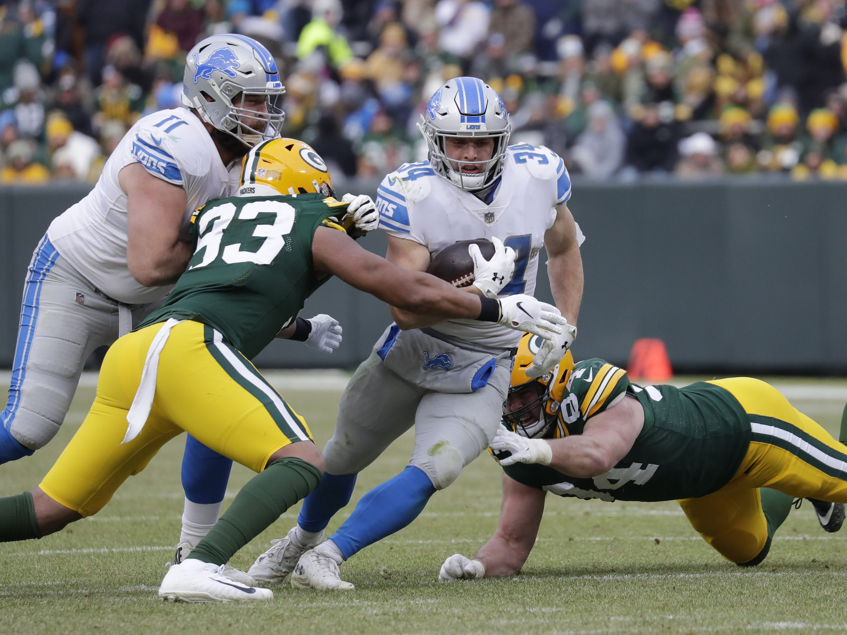 Detroit Lions running back Zach Zenner (34) runs against Green Bay Packers linebacker Reggie Gilbert (93) and defensive end Dean Lowry (94) in the fourth quarter Sunday, December 30, 2018, at Lambeau Field in Green Bay, Wis.  Dan Powers/USA TODAY NETWORK-Wisconsin