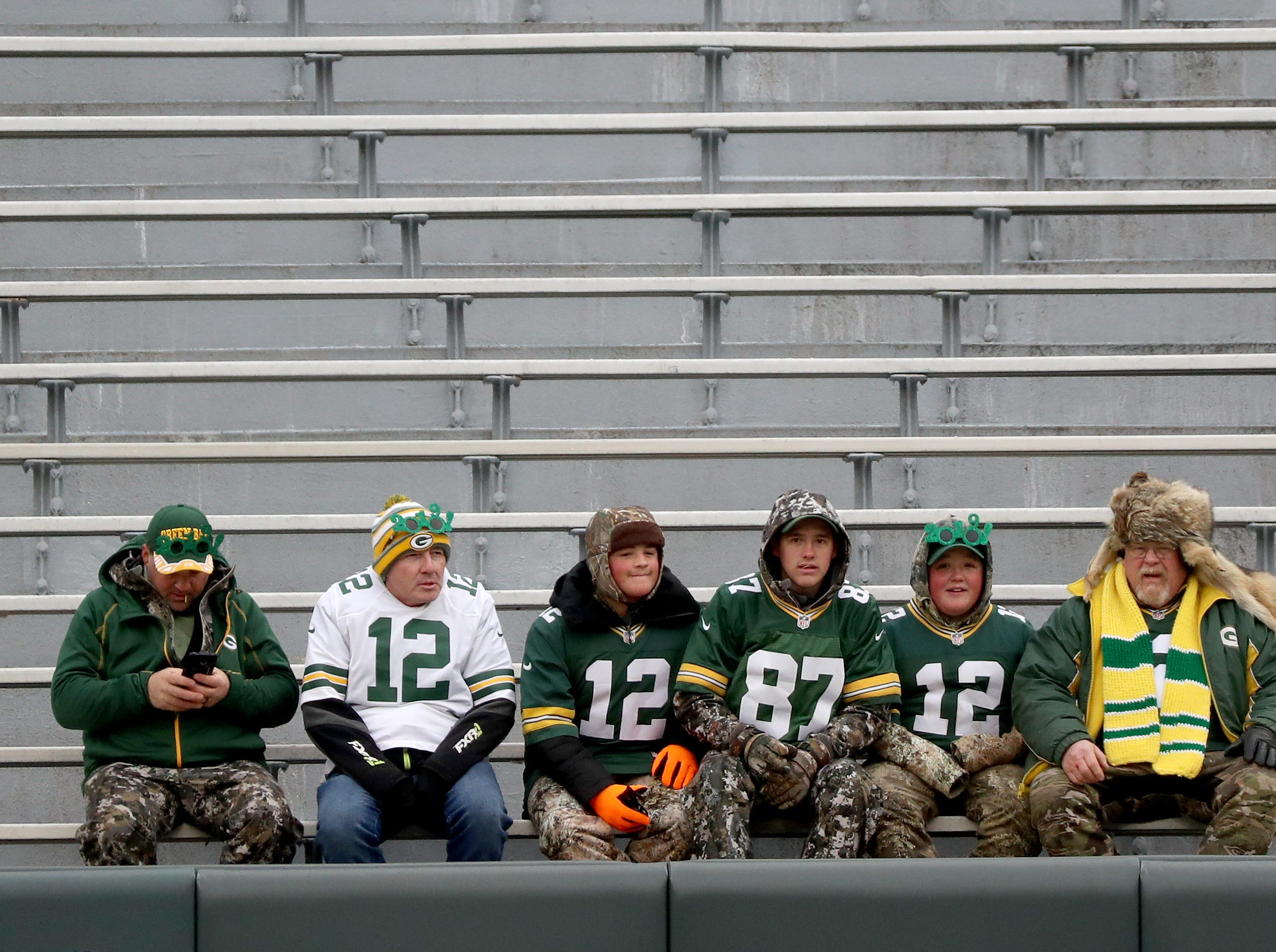 Early arriving fans in their best camo claim their seats before the game against the Detroit Lions at Lambeau Field Sunday, December 30, 2018 in Green Bay, Wis.