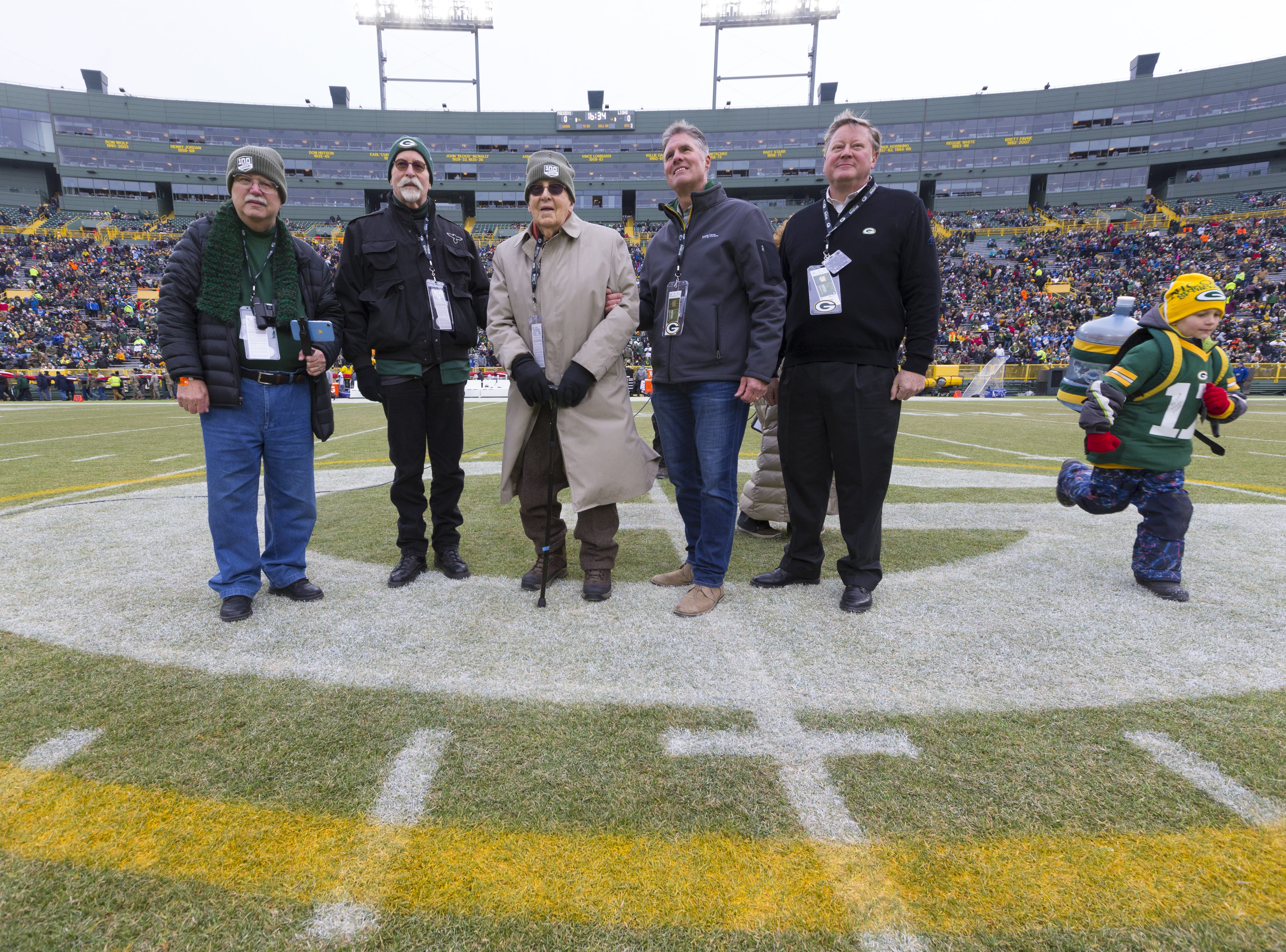 Eugene Nordby (center), who served as a military surgeon during World War II, is honored at midfield before the Green Bay Packers game against the Detroit Lions Sunday, December 30, 2018 at Lambeau Field in Green Bay, Wis. Nordby is the same age as the Packers - 100 years. Nordby graduated from Luther College in 1939 and earned his medical degree at UW-Madison in 1943. He served as a captain in the U.S. Army Medical Corps, 1944-46 and then practiced as an orthopedic surgeon until 1981. Second from left is Nordby's son, Jon.  MARK HOFFMAN/MILWAUKEE JOURNAL SENTINEL