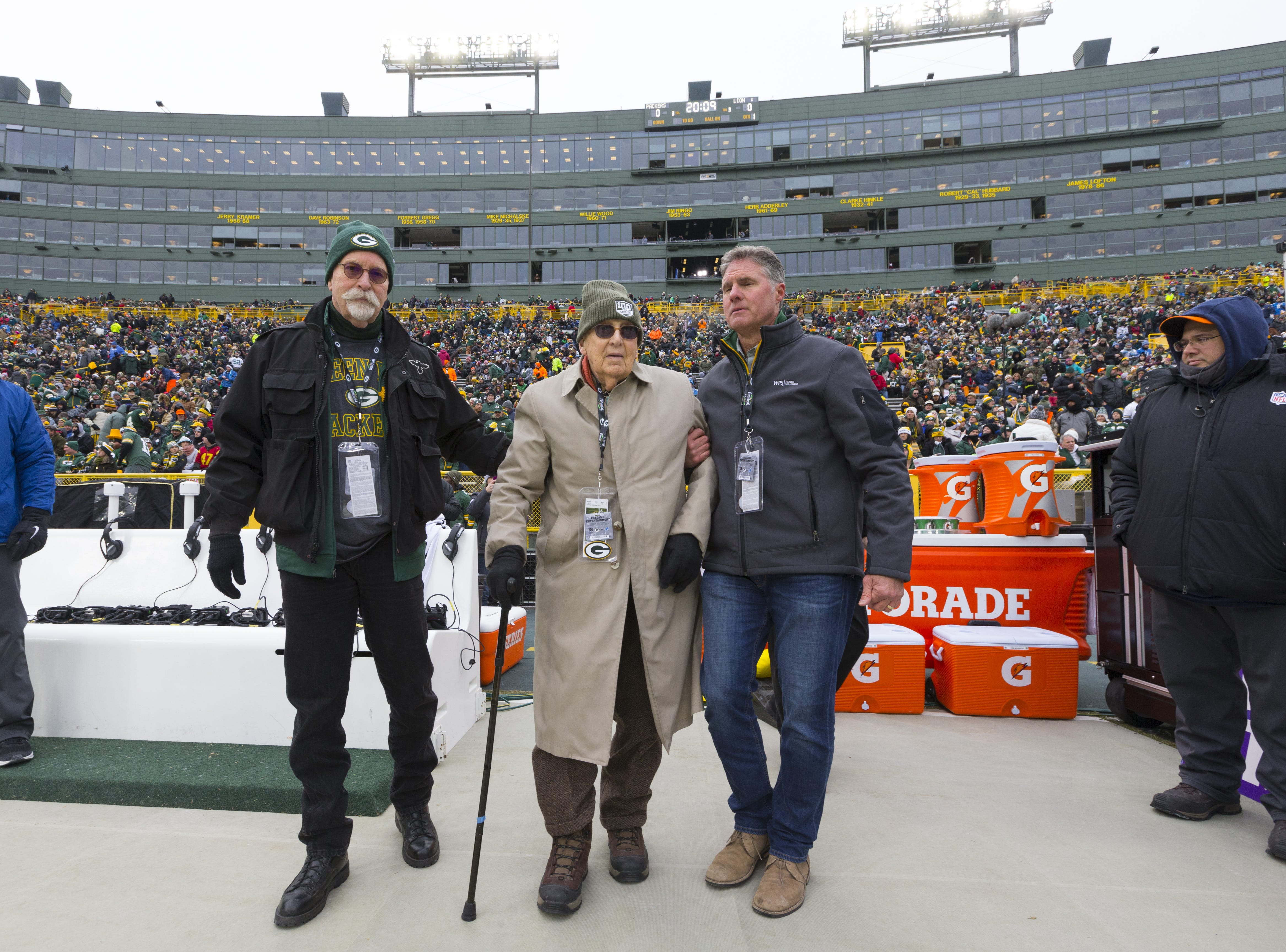 Eugene Nordby (center), who served as a military surgeon during World War II, is escorted to midfield to be honored before the Green Bay Packers game against the Detroit Lions Sunday, December 30, 2018 at Lambeau Field in Green Bay, Wis. Nordby is the same age as the Packers - 100 years. Nordby graduated from Luther College in 1939 and earned his medical degree at UW-Madison in 1943. He served as a captain in the U.S. Army Medical Corps, 1944-46 and then practiced as an orthopedic surgeon until 1981. On the left is Nordby's son, Jon.  MARK HOFFMAN/MILWAUKEE JOURNAL SENTINEL