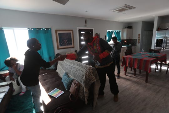Visitors arrive at the Maat home in Desert Hot Springs to celebrate Ujamaa (Cooperative Economics) day of Kwanzaa on Saturday, December 29, 2018.