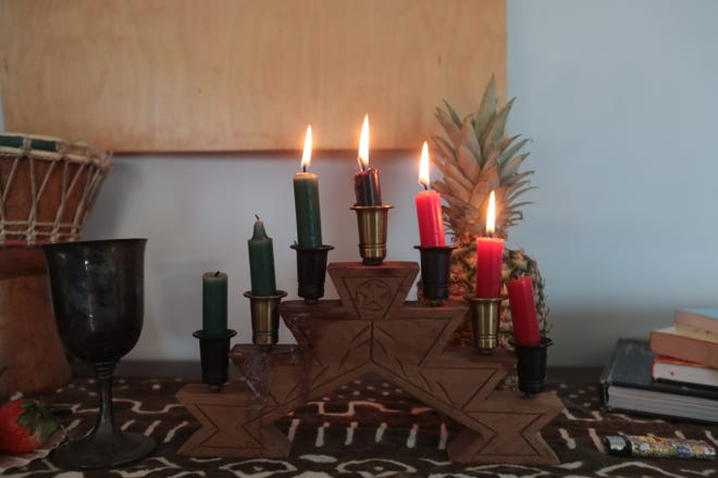 The seven candles on the kinara represents the seven core principles of Kwanzaa.  Saturday, December 29, 2018. Four candles are lit on the fourth day of Kwanzaa. The black candle in the center represents the African people, the red candles represents their struggle and the greens their  future and hope.